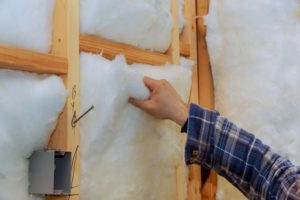 worker in insulating rock wool insulation in wooden frame for future house wall for comfortable warm